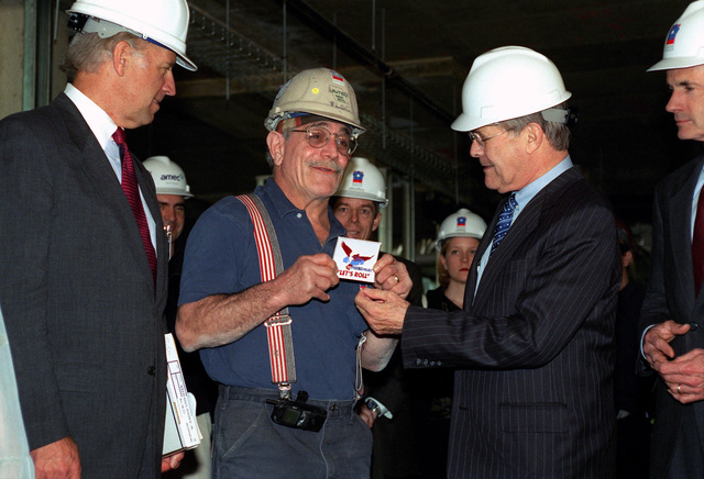 "The Honorable Donald H. Rumsfeld (2nd from right), U.S. Secretary of Defense, presents a decal with the Project Phoenix""Let's Roll""logo, to sheet metal worker Michael Flocco (2nd from left) at the Pentagon, Arlington, Va., on Apr. 10, 2002.  The Honorable Senators of Delaware, Democrats Joseph Biden (left) and Thomas Carper (right) were also in attendance. (DoD photo by Robert D. Ward) (Released"