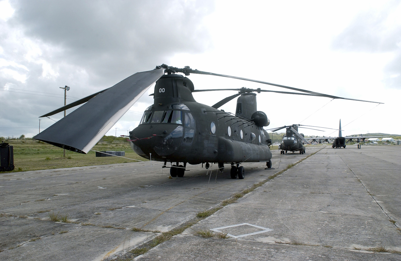 Two CH-47 Chinook helicopters from the Nevada Army National Guard (ANG), Detachment 1, Company G, 140th Aviation and a US Air Force (USAF) C-130 cargo aircraft from the Tennessee ANG, 118th Air Wing (AW), from Nashville, sit on the tarmac at the Bird International Airport, during the Tradewinds 2002 Field Training Exercise (FTX), on the island of Antigua
