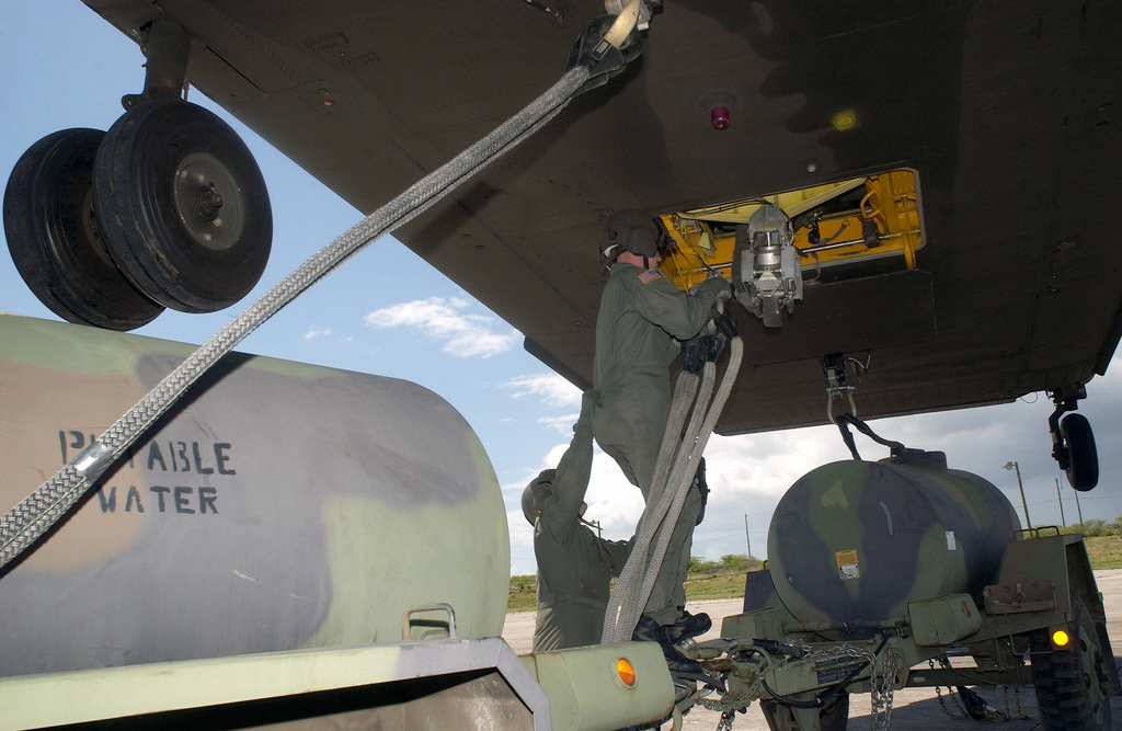 """US Army (USA) Sergeant (SGT) Robert Dashiell, top and SPECIALIST First Class (SFC) Scott Ellis, from Detachment 1, Company G, 140th Aviation, Nevada Army National Guard (ANG), hookup a pair of M-149 400-gallon """"Water Buffalos"""" to a hovering CH-47 Chinook helicopter, at the V.C. Bird International Airport, during the Tradewinds 2002 Field Training Exercise (FTX), on the island of Antiqua"""