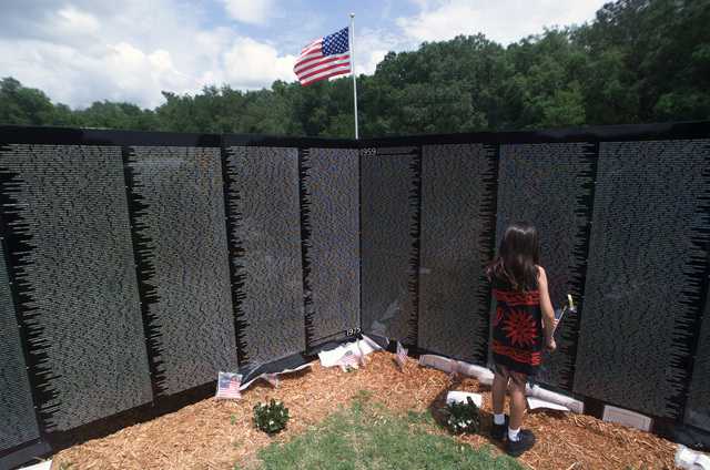 A young girl views the names of fallen warriors on the Vietnam Memorial moving wall, during the 9th Annual Salute to Vietnam Veterans held at Edward Medard Park near Plant City, Florida, on April the 13th, 2002