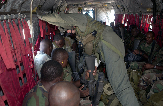 Soldiers from the 1ST Caribbean Battalion are assisted with their seatbelts by a CH-47 Chinook helicopter crewmember from Detachment, 1ST Battalion, 228th Aviation Regiment (AR), Fort Buchanan, Puerto Rico, during the Tradewinds 2002 Field Training Exercise (FTX)