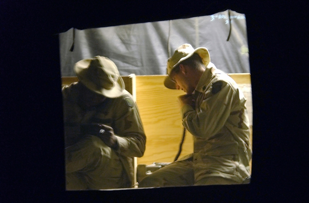 Two US Army soldiers make morale calls to their familiesΘ back home on 13 April 2002. The phone tent consists of six phones used by the 3,000 personnel on temporary duty (TDY) here at Kandahar Air Base, Afghanistan, in support of Operation ENDURING FREEDOM. Each member is authorized a 15-minute phone call per week