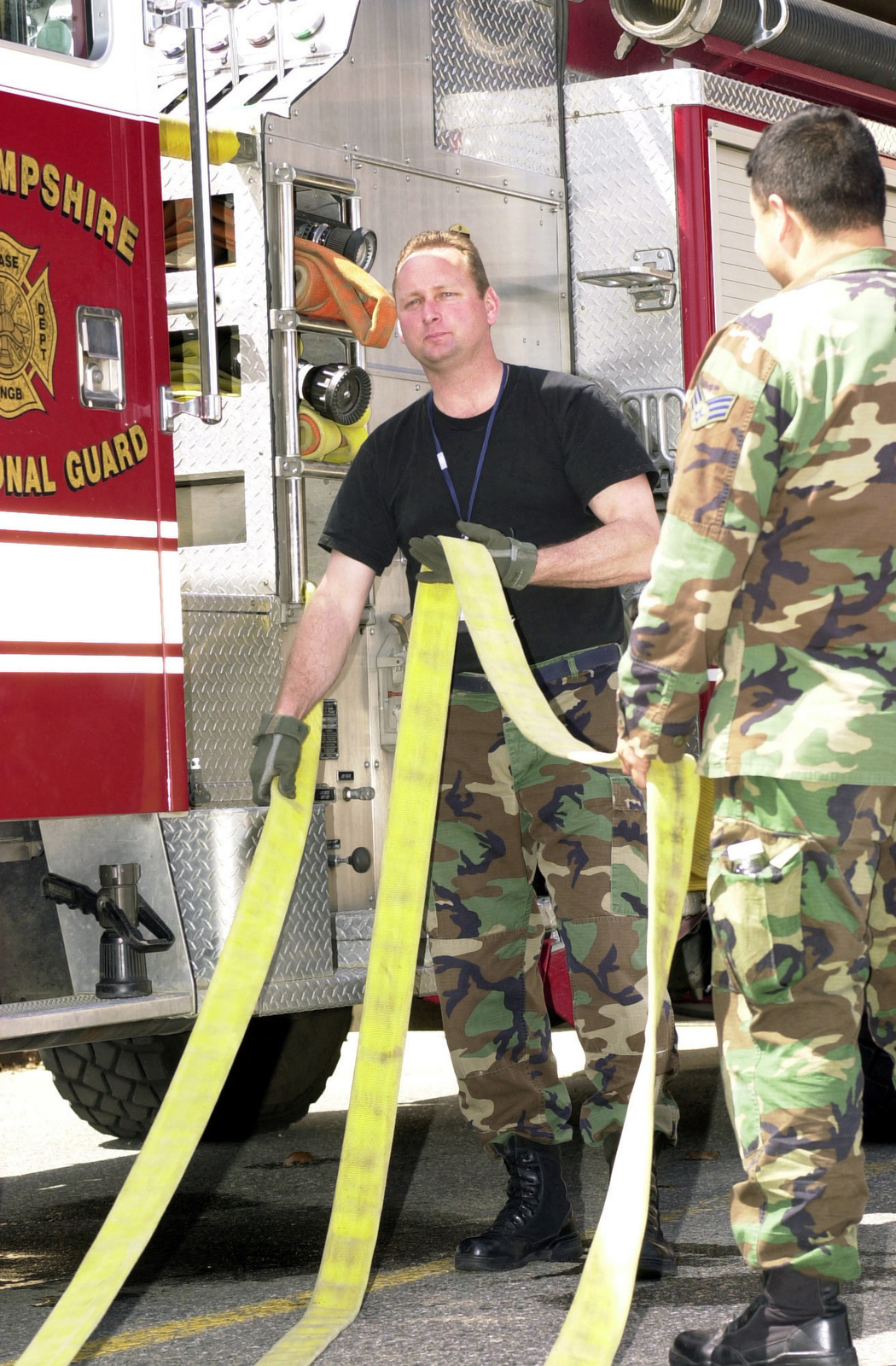 US Air Force (USAF) personnel assigned to the 157th Air Refueling Wing (ARW) Fire Department, New Hampshire (NH), Air National Guard (ANG) rewind fire hose onto the truck, during a training exercise conducted at Pease Air National Guard Base (ANGB), NH