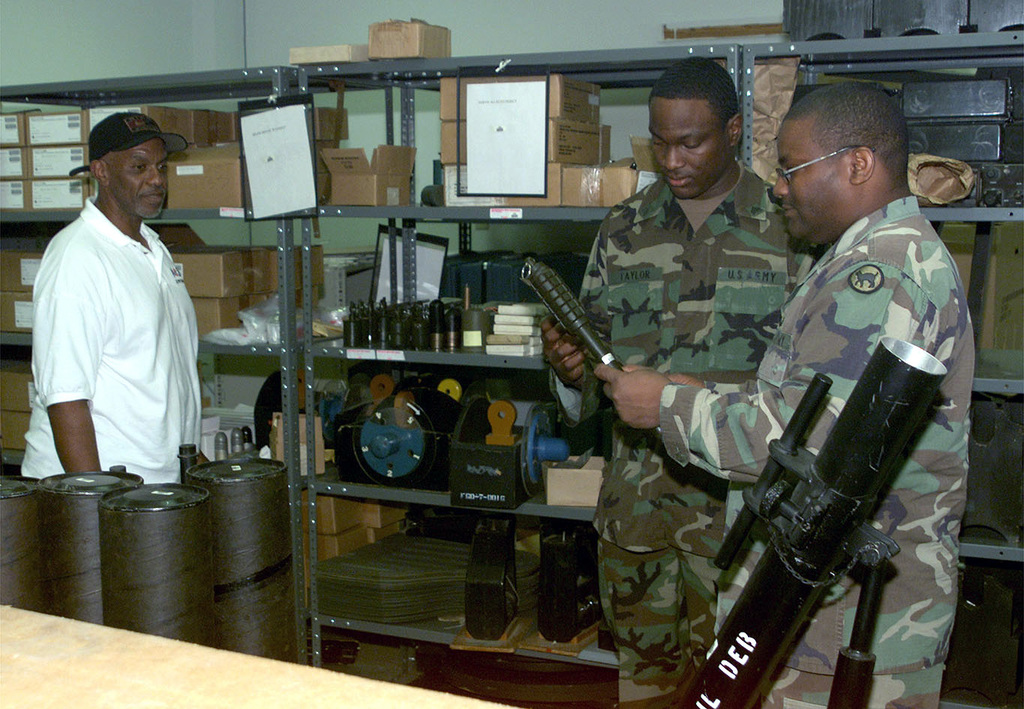 Mr. Thomas Henderson, US Army (USA) Training Support Center (TSC) Supply Clerk, look on as two USA soldiers inspect Training Aids, Devices, Simulators & Simulation (TADSS) equipment at the TSC, Fort Gordon, GA