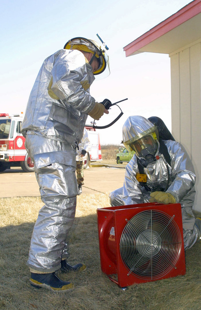 Firefighters, in full proximity suit, 148th Fighter Wing (FW), 148th Civil Engineer Squadron (CES), Minnesota Air National Guard (MNANG), start an electric fan to assist them in navigating through a smoke filled building. The airmen, activated in support of Operation NOBLE EAGLE, are conducting training exercises as part of a larger Search and Rescue/Structural Response Scenario