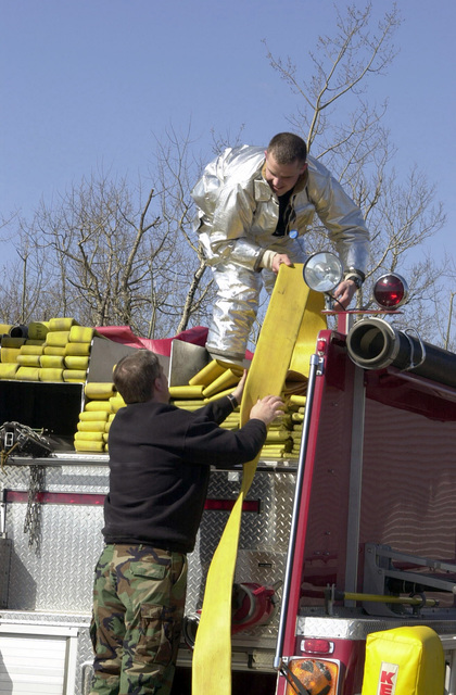 Firefighters, one in full proximity suit, 148th Fighter Wing (FW), 148th Civil Engineer Squadron (CES), Minnesota Air National Guard (MNANG), repack the fire hose back onto their fire truck following a training exercise. The airmen, activated in support of Operation NOBLE EAGLE, are conducting training exercises as part of a Ventilation Exercise/Structural Response Scenario