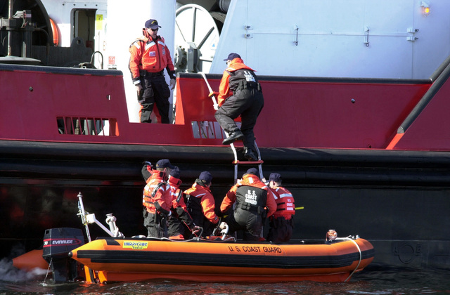 Members of a United States Coast Guard (USCG) Law Enforcement vessel boarding team and Special Agents from the Federal Bureau of Investigations (FBI) board a suspicious vessel from a Rigid Hull Inflatable (RIB) boat, during maritime operations in the Port of Valdez, Alaska, in support of exercise Northern Edge 2002