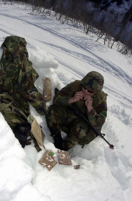 PETTY Officer Third Class (PO3) Justin Gomez, a member of the Naval Mobility Construction Battalion 4 (NMCB4) Port Hueneme, California, takes a break from standing watch for a Meal Ready to Eat or MRE, during a civilian and military mass causality exercise at the Alyeska Pipeline in Valdez, Alaska hosted by the Alaskan Command, during exercise NORTHERN EDGE 2002