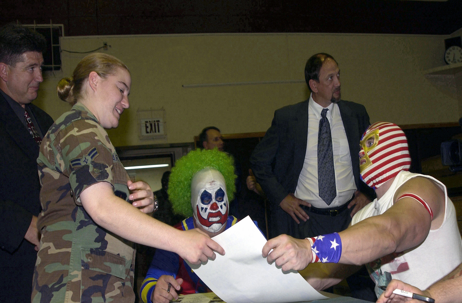 """US Air Force (USAF) AIRMAN First Class (A1C) Danielle Hawthorn (foreground left), 39th Security Forces Squadron (SFS), receives a signed autograph from Professional Wrestlers from the World Wrestling Alliance (WWA), Doink """"The Clown"""" (center) and The Patriot (right), prior to an Armed Forces Entertainment (AFE) sponsored event held at Incirlik Air Base (AB), Turkey"""