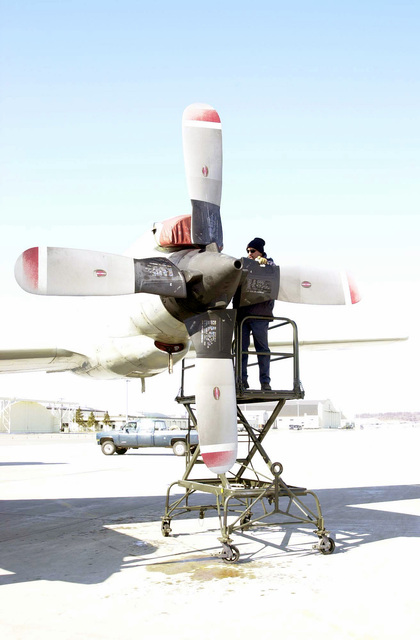 Jun Lantaya, SENIOR Technician assigned to the Naval Air Warfare Center (NAWC), Point Mugu, California, checks a magnetic plug on an NP-3D Orion engine, during a post flight check-up on the flight line of Elmendorf Air Force Base (AFB), Alaska