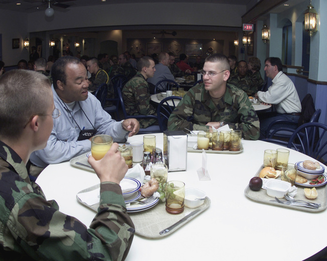 Mister Tyrone Taborn, CHIEF Executive Officer (CEO), Career Communications Group Inc., enjoys a US Air Force (USAF) breakfast with technical school students AIRMAN Basic (AB) John Droppa, right and AB John Calamara, left, during a private tour for the members of the Joint Civilian Orientation Conference at Sheppard Air Force Base (AFB), Texas