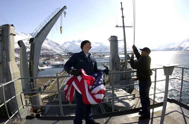 Signalman (SM), PETTY Officer Third Class (PO3) Kristopher Boyette, shifts the mooring and shifting colors to show that a ship has been moored on amphibious transport dock USS DUBUQUE (LPD 8) as it arrives at the Port of Valdez, Alaska, in support of exercise Northern Edge 2002