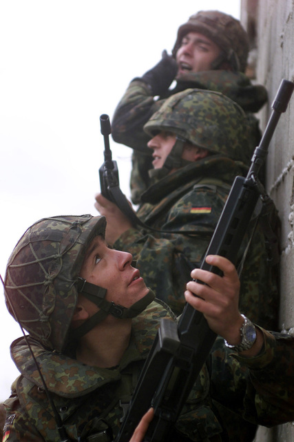 During exercise Joint Resolve 26, in Bosnia and Herzegovina (BiH), soldiers armed with Heckler and Koch automatic assault rifles from the German Battle Group's 2nd Reinforced Infantry Company, enter a building suspected of containing French soldiers role playing paramilitary extremists
