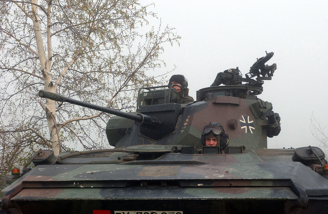 During exercise Joint Resolve 26, in Bosnia and Herzegovina (BiH), soldiers from the German Battle Group's 2nd Reinforced Infantry Company, in their Spahpanzer Luchs 2 armored reconnaissance vehicle seek to capture French soldiers playing the role of paramilitary extremists, near a paramilitary training camp in the town of Pazaric