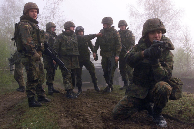 During exercise Joint Resolve 26, in Bosnia and Herzegovina (BiH), soldiers from the German Battle Group's 2nd Reinforced Infantry Company role play with French soldiers near a paramilitary training camp in the town of Pazaric