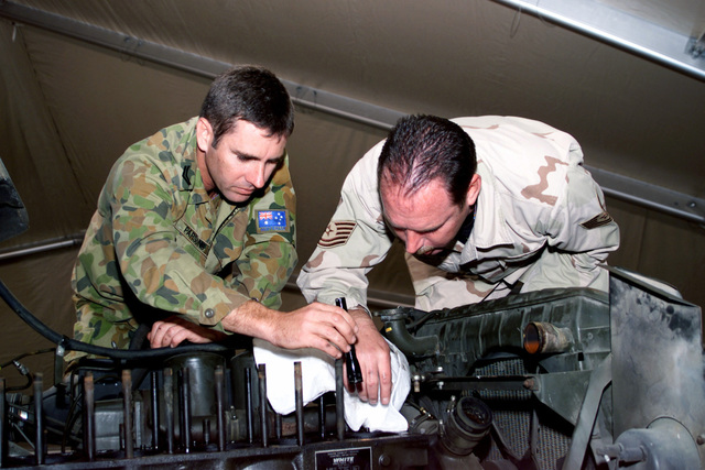 US Air Force (USAF) Technical Sergeant (TSGT) Cullen Lawrence, a Non-Commissioned Officer in Charge (NCOIC) of Vehicle Maintenance and Royal Australian Air Force, Corporal (CPL) Tony J. Parsons, a Ground Support Equipment Technician, examine an engine block on an M-Series 2 1/2 ton truck at Peter J. Ganci Jr. Air Base, Kyrgyzstan, in support of Operation ENDURING FREEDOM
