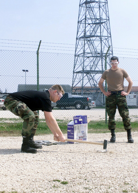United States Air Force (USAF) AIRMAN First Class (A1C) Jason Hirst, assigned to the 31st Communications Squadron (CS), Aviano Air Base, Italy, smashes a computer hard drive with a sledge hammer in order to render destroy it, as A1C Aaron Billingsley, observes