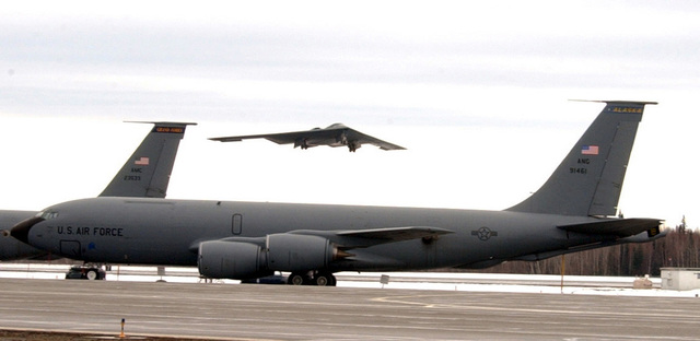 A KC-135 Stratotanker sits on a ramp while a B-2 Spirit bomber from Whiteman Air Force Base (AFB), Missouri, takes off from Eielson AFB, Alaska, in support of exercise Northern Edge 2002