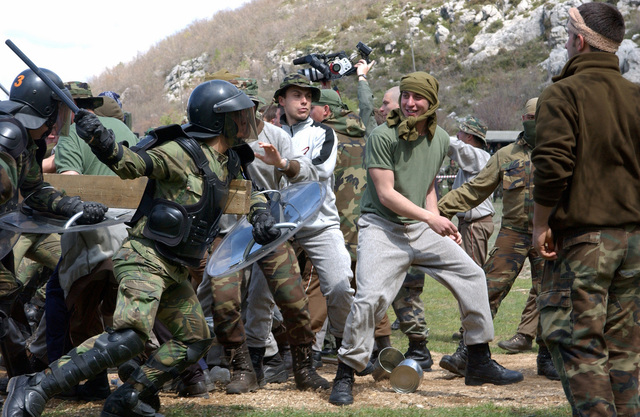 A Reaction Force made up of Portuguese Army, Operational Reserve (OPRES) Forces dressed in personal protective armor respond to an angry mob during a simulated riot and crowd control exercise at Trebinje, Bosnia and Herzegovina (BiH), during Exercise JOINT RESOLVE 26