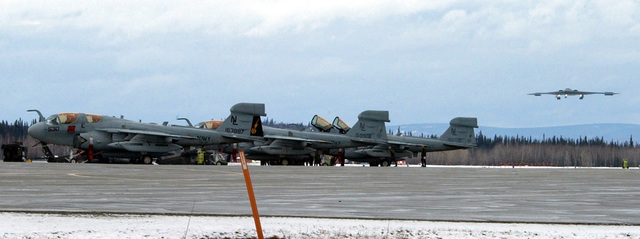 US Navy (USN) EA-6B Prowlers sits on the flight line, while a B-2 Spirit bomber from Whiteman Air Force Base (AFB), Missouri, lands at Eielson AFB, Alaska, after completing a mission in support of exercise Northern Edge 2002