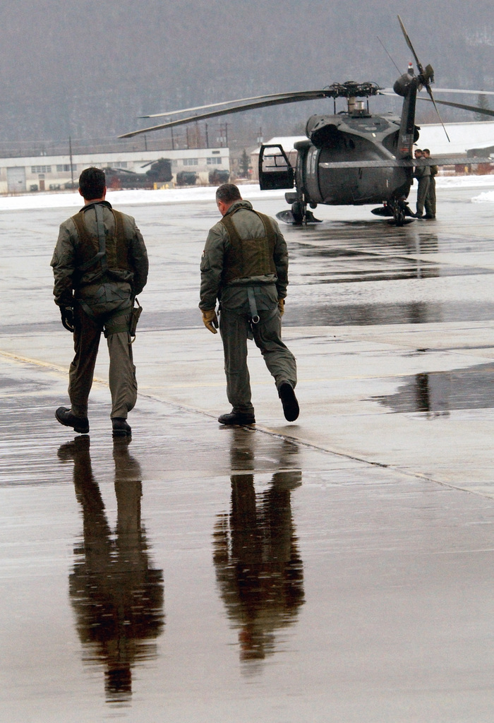 Two US Army (USA) HH-60 Black Hawk helicopter Pilots assigned to the 207th Aviation Battalion, Alaska Army National Guard (ANG), walk across the flight line at Fort Richardson Army Base, Alaska, after all of their flights and training were temporarily placed on hold due to bad weather, during Exercise NORTHERN EDGE 2002