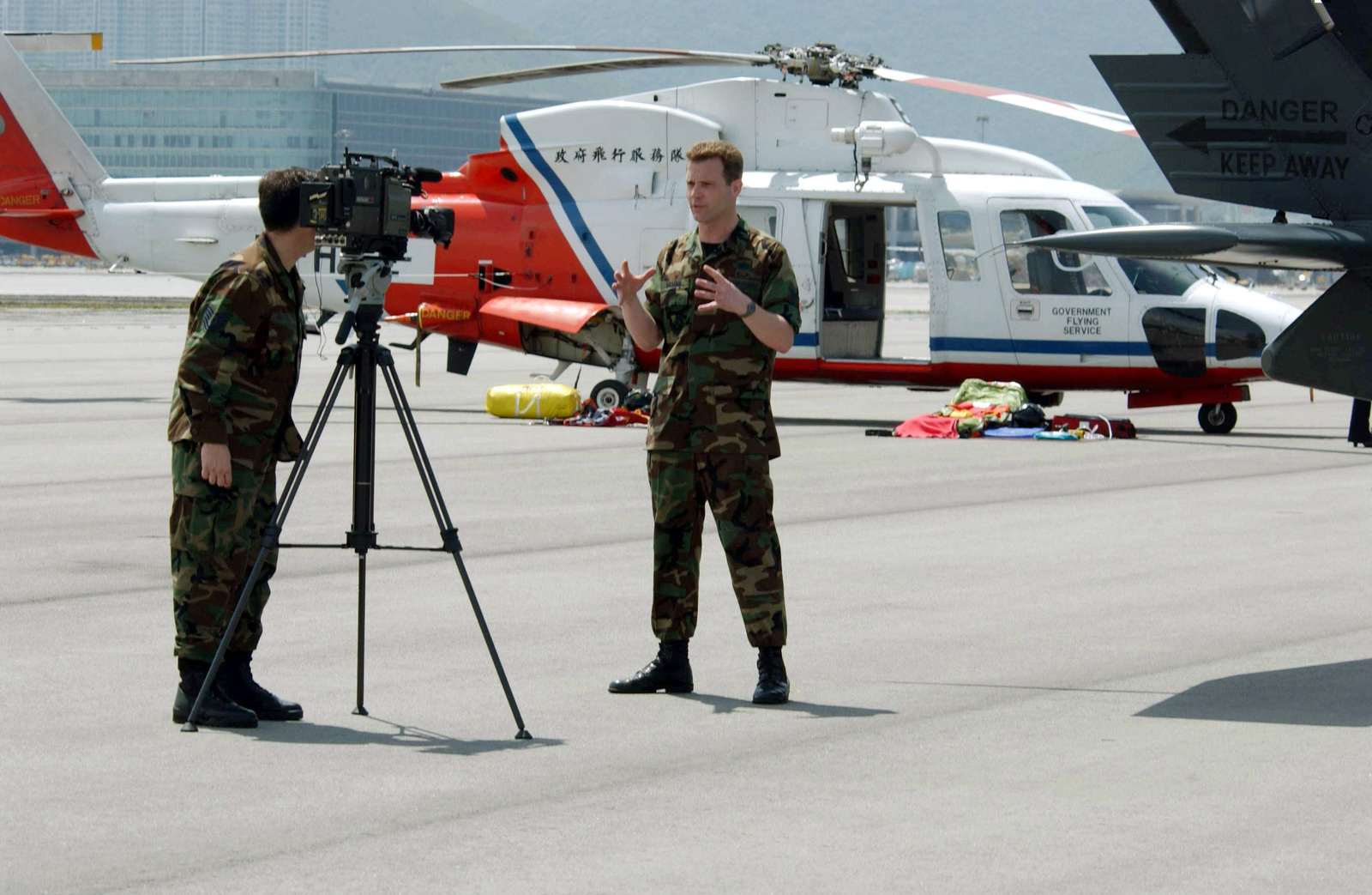 US Air Force (USAF) Technical Sergeant (TSGT) Mark Hatfield (left) uses a video camera to record USAF STAFF Sergeant (SSGT) Michael Brogan, during a stand-up interview on the flight line at Hong Kong International Airport. TSGT Hatfield and SSGT Brogan are both assigned to Detachment 10 American Forces Network-Tokyo, Yokota Air Base, Japan, and are covering the annual Hong Kong Search and Rescue Exercise. A Japan Self Defense Force (JASDF) UH-60J Search and Rescue helicopter is parked in the background