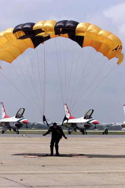 A member of the US Army (USA) Golden Knights Parachute team lands right on the mark, on the flight line at Eglin Air Force Base (AFB) Florida (FL), during the annual Open House and Air Show. Several F-16 Fighting Falcon aircraft from the US Air Force (USAF) Thunderbirds aerial demonstration are parked in the background