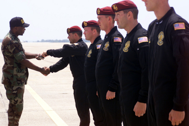 US Air Force (USAF) Lieutenant Colonel (LTC) Hicks (left), Air Show Director, accepts a Baton from a member of the US Army (USA) Golden Knights Parachute team, during the annual Open House and Air Show held at Eglin Air Force Base (AFB) Florida (FL)