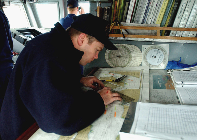 US Coast Guard (USCG) PETTY Officer First Class (PO1) Jeff Morgan, uses navigational aids to plot the ships course on the bridge aboard the USCG ISLAND CLASS, Patrol Craft, USS MUSTANG (WPB 1310), while the ship is underway at Port Valdez, during Exercise NORTHERN EDGE 2002