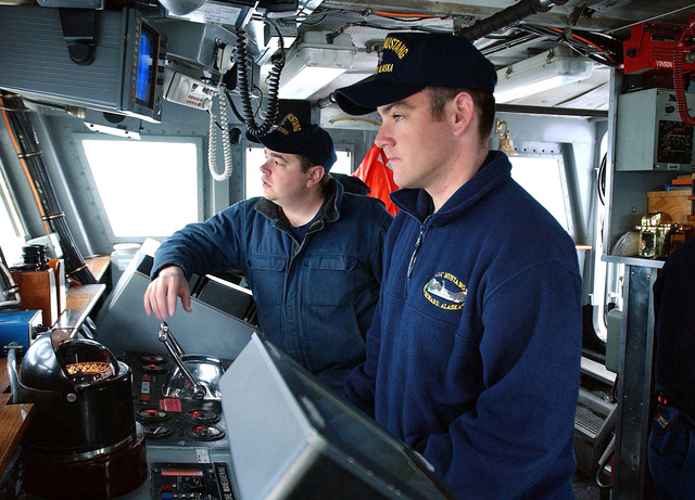 US Coast Guard (USCG) PETTY Officer Second Class (PO2) Eamon McCormack (foreground) and PETTY Officer (PO) Joel Ware, man the bridge aboard the USCG ISLAND CLASS, Patrol Craft, USS MUSTANG (WPB 1310), while the ship is underway at Port Valdez, during Exercise NORTHERN EDGE 2002