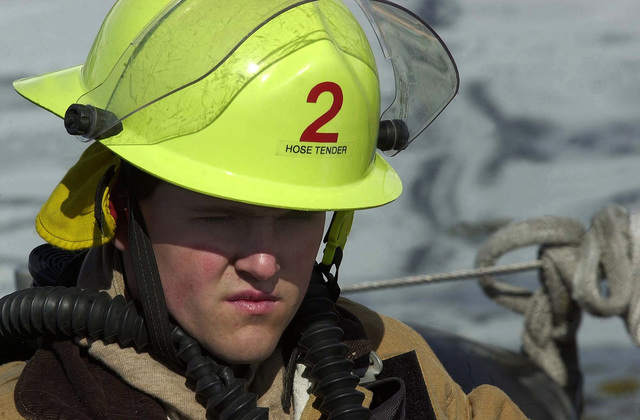 US Coast Guard (USCG) PETTY Officer Third Class (PO3) Jeremy McKeage, prepares for a fire fighting drill aboard the US Coast Guard (USCG) ISLAND CLASS, Patrol Craft, USS MUSTANG (WPB 1310), while underway at Port Valdez, Alaska, during Exercise NORTHERN EDGE 2002