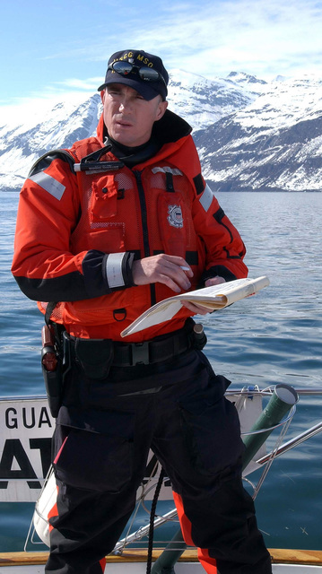 US Coast Guard (USCG) PETTY Officer Third Class (PO3) Mark Whitman, assigned to the Port Valdez, Alaska, Marine Safety Office checks the ships manifest aboard the civilian vessel Kindred Spirit, after the vessel was boarded for entering a restricted area during Exercise NORTHERN EDGE 2002