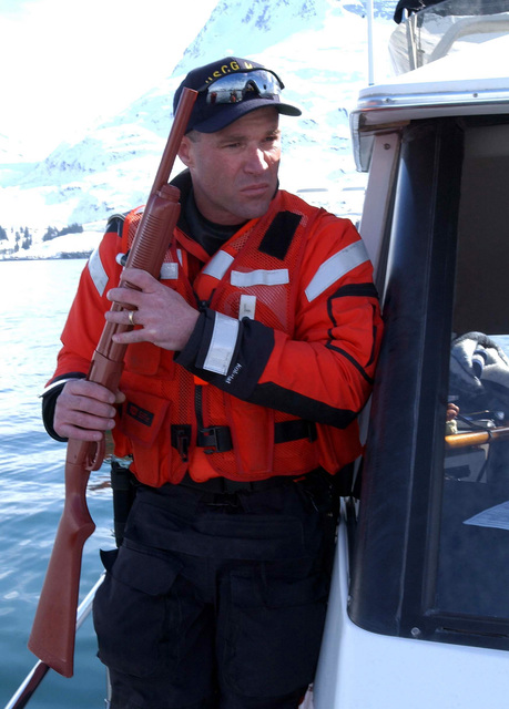 US Coast Guard (USCG) PETTY Officer Third Class (PO3) Tom Demi, assigned to the Port Valdez, Alaska, Marine Safety Office, armed with a 12-gauge shotgun stand guard during the board and search of the civilian vessel Kindred Spirit, during Exercise NORTHERN EDGE 2002