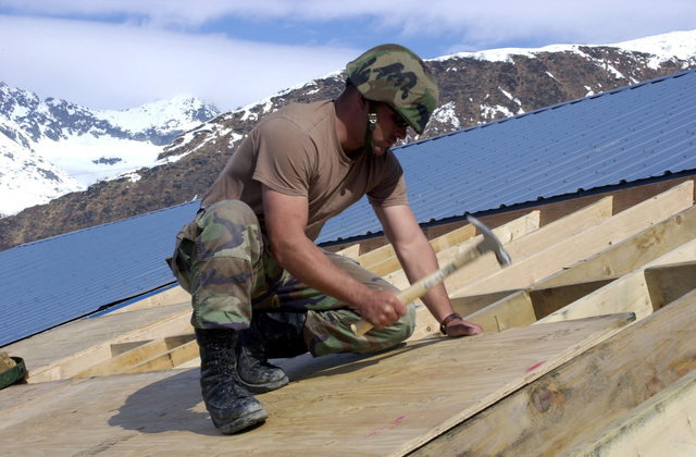 US Navy (USN) PETTY Officer Third Class (PO3) Curtis Elder, a Constructionman (CN) assigned to Naval Mobile Construction Battalion 4 (NMCB-4,) nails down plywood for the new roof on the Valdez Animal Shelter, at Port Valdez, Alaska, during Exercise NORTHERN EDGE 2002