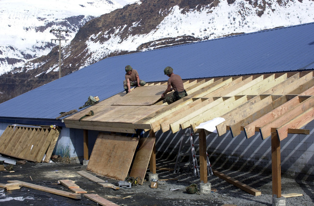 US Navy (USN) PETTY Officer Third Class (PO3) Curtis Elder (left), a Constructionman (CN) assigned to Naval Mobile Construction Battalion 4 (NMCB-4,) and USN SEAMAN (SN) Jason Oxay, a Steelworker (SW) also assigned to NMCB-4, nails down plywood for the new roof on the Valdez Animal Shelter, at Port Valdez, Alaska, during Exercise NORTHERN EDGE 2002