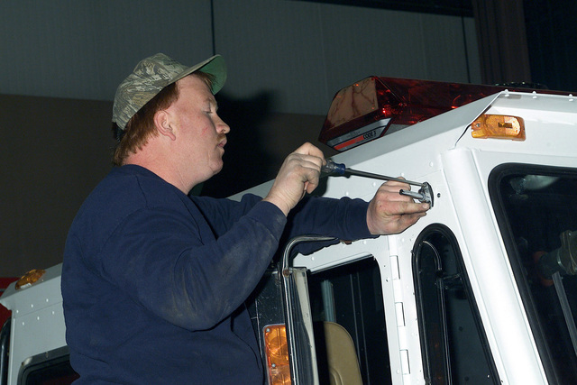 Bart Culpitt, automotive mechanic, Installation Materiel Maintenance Activity, Directorate of Supply and Services, installs a spotlight on a 2500L series fire engine. The fire engine is being donated to the New York Fire Department after the damage their vehicles during the September 11th terrorist attacks