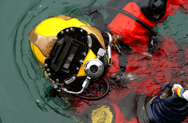 US Navy (USN) Diver, PETTY Officer Third Class (PO3) Ken Waiting, assigned to Detachment 1 (DET1), Mobile Diving and Salvage Unit 1 (MDSU-1), is lowered into the water during a pier repair operations dive at Port Valdez, Alaska, during Exercise NORTHERN EDGE 2002