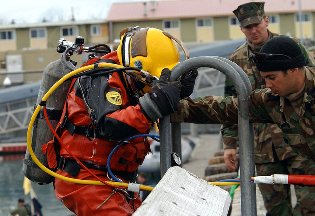 US Navy (USN) Diver, PETTY Officer Third Class (PO3) Ken Waiting (left), assigned to Detachment 1 (DET1), Mobile Diving and Salvage Unit 1 (MDSU-1), is assisted by USN PETTY Officer First Class (PO1) Aristoteli Dorizaz, as he descends the diving ladder during a pier repair operation dive at Port Valdez, Alaska, during Exercise NORTHERN EDGE 2002