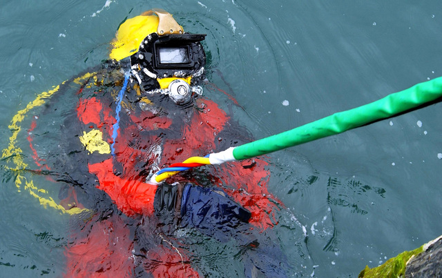 US Navy (USN) Diver, PETTY Officer Third Class (PO3) Michael Davis, assigned to Detachment 1 (DET1), Mobile Diving and Salvage Unit 1 (MDSU-1), is lowered into the water during a pier repair operation dive at Port Valdez, Alaska, during Exercise NORTHERN EDGE 2002