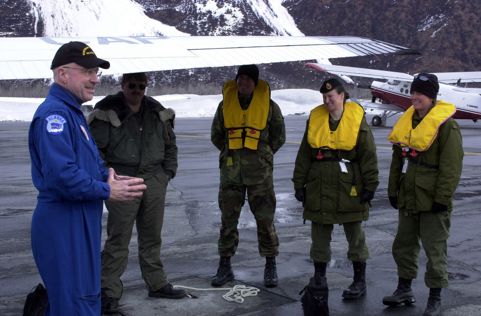 Mr. H. A. Horvath (left), a member of the US Air Force (USAF) Civil Air Patrol (CAP), gives a preflight briefing to Mr. Larry Huling, CAP; US Navy (USN) PETTY Officer First Class (PO1) Troy Roat, assigned to Detachment 1 (DET1), Mobile Diving and Salvage Unit 1(MDSU-1); Royal Canadian Navy (RCN) MASTER Corporal Debra Bowcott; and RCN Leading SEAMAN (LS) Kerri Edison, assigned to the Port Inspection Dive Team (PIDT), Esquimalt, British Columbia; before a flight at Port Valdez, Alaska, during Operation NORTHERN EDGE 2002. A Garmin AN-2 bi-plane is visible in the background