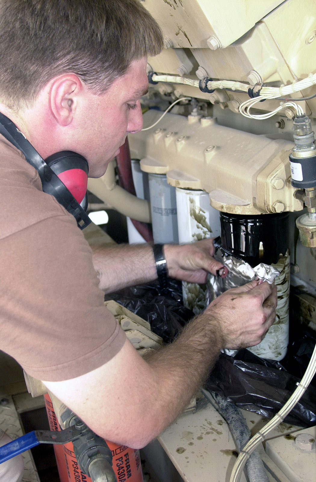 US Air Force (USAF) STAFF Sergeant (SSGT) Jonathan Quigley, Power Production SPECIALIST, 186th Civil Engineering Squadron (CES) Mississippi Air National Guard (ANG), changes the oil filters on a MEP-12 generator compressor at an undisclosed location in support of Operation ENDURING FREEDOM