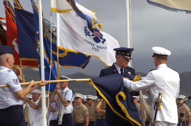 General Richard B. Myers, USAF, Chairman of the Joint Chiefs of STAFF, and Commander-in-CHIEF US Pacific Command Admiral Dennis C. Blair attach a streamer to the Pacific Commands flag during the Change of Command Ceremony for the Commander-in-CHIEF US Pacific Command at Marine Corps Base, Kaneohe Bay, Hawaii. During the Ceremony Admiral Dennis C. Blair relinquished his command to Admiral Thomas B. Fargo