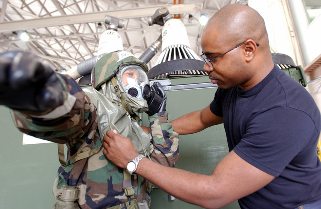 US Air Force (USAF) AIRMAN First Class (A1C) Summer Rawls (left), get aid from USAF Technical Sergeant (TSGT) Jerome Brittingham, as she dons her Mission-Oriented Protective Posture response level 4 (MOPP-4) gear, during a chemical alert drill. A1C Rawls and TSGT Brittingham as both assigned with the 6th Supply Squadron deployed at Homestead Air Reserve Base (ARB), Florida (FL)