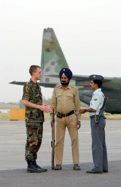 US Air Force (USAF) SENIOR AIRMAN (SRA) Jeremy Henderson (left), Weather Technician assigned to the 353rd Operations Support Squadron (OSS), discuss the ongoing joint combined exchange training with Indian Air Force (IAF) Sergeant (SGT) Satadal Mandal and Prit Singh, on the flight line at Air Force Station Agra, India. Members of the 353rd OSS are deployed here for three weeks of joint combined exchange training with the Indian Armed Forces. IAF SGT Singh is armed with a 9mm L2A3 Sterling sub-machine gun and IAF SGT Mandal carries a 7.62mm IMBEL semi-automatic rifle