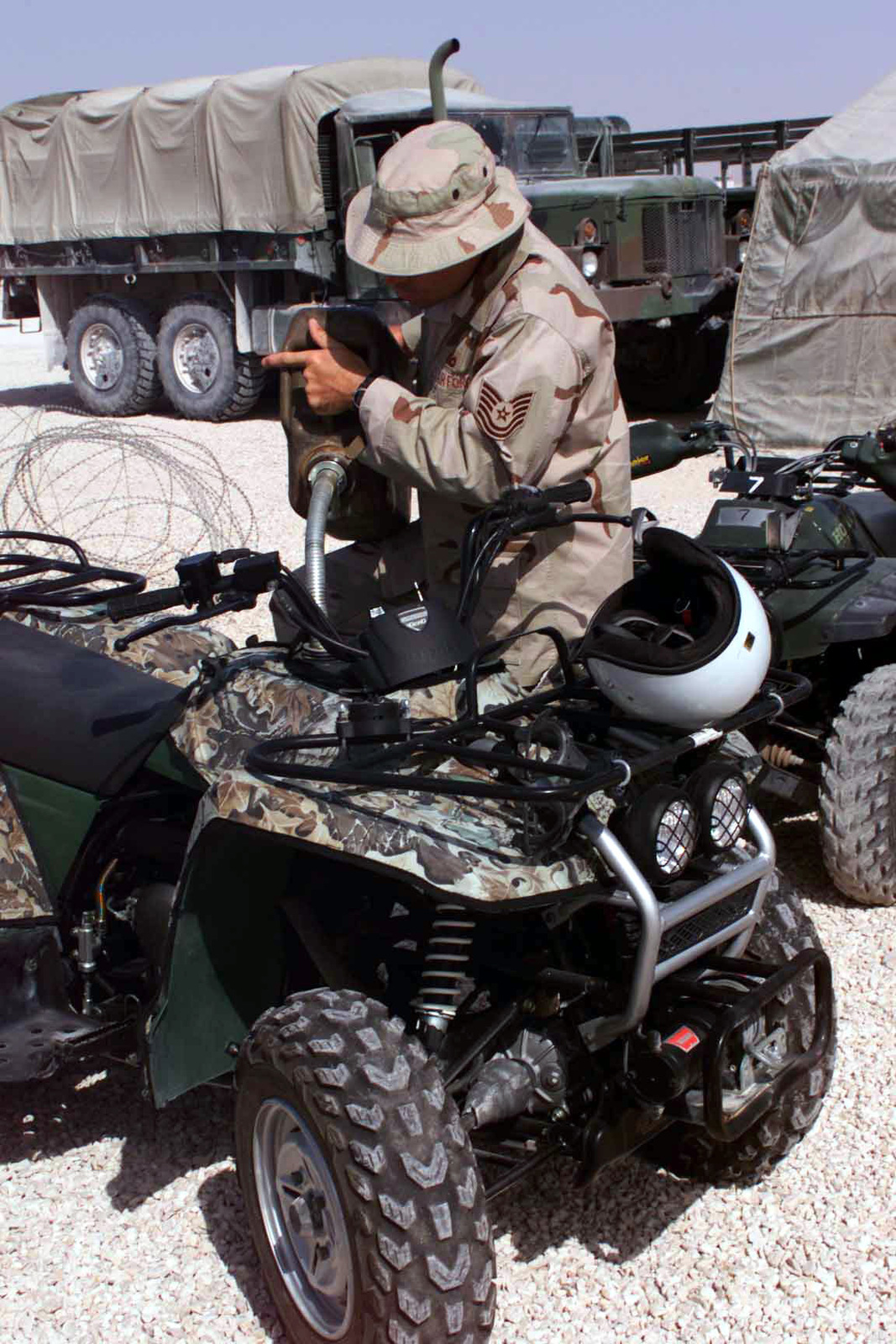 US Air Force (USAF) Technical Sergeant (TSGT) Ronzil D. Starcher, 379th Expeditionary Security Forces Squadron (ESFS), refuels an All Terrain Vehicle (ATV) in preparation for an ATV class conducted at Al Udeid Air Base (AB), Qatar, during Operation ENDURING FREEDOM