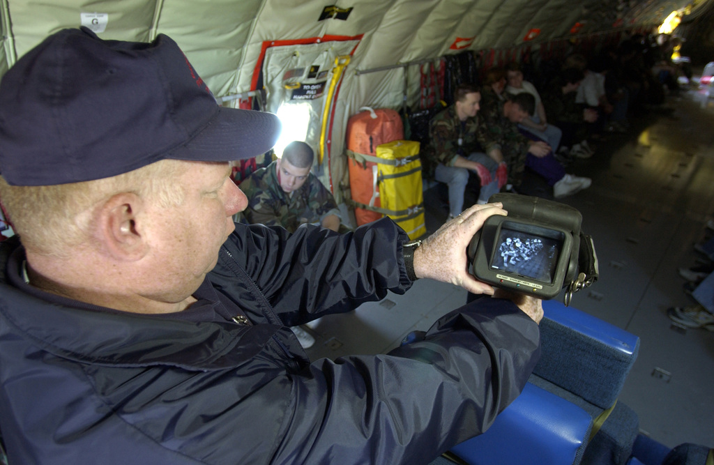 Mr. Mark Foley, Fire-Rescue Instructor, Barnstable County, Massachusetts (MA) uses a thermal imaging device to transmit live video images of simulated casualties, to the emergency control center, from inside the cargo compartment of a US Air Force (USAF) KC-135 Stratotanker aircraft, during a mass casualty exercise conducted by the102nd Fighter Wing (FW), Massachusetts (MA), Air National Guard (ANG), on the flight line at Otis, Air National Guard Base (ANGB), MA