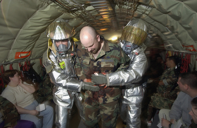 US Air Force (USAF) Firefighters assigned to the 102nd Civil Engineering Squadron (CES), Massachusetts (MA), Air National Guard (ANG), assist a simulated casualty victim during a mass casualty exercise conducted aboard a USAF KC-135 Stratotanker aircraft, on the flight line at Otis, Air National Guard Base (ANGB), MA