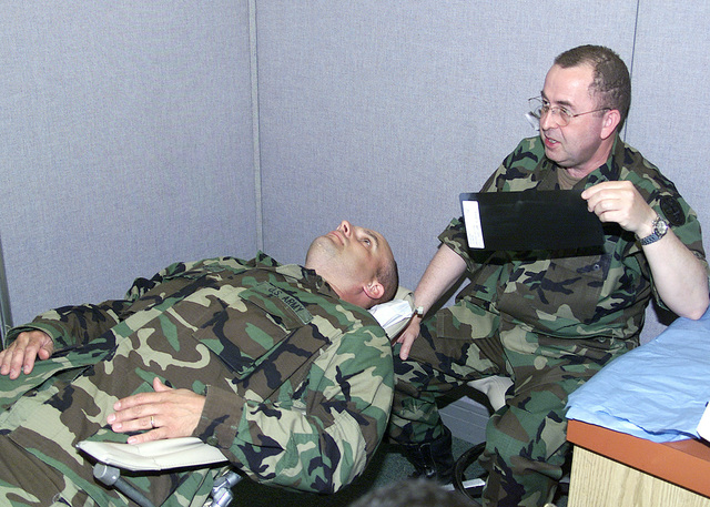 A soldier with 1ST Battalion, 69th Infantry (1/69) listens as the dentist explains details of his Panograph (Panoramic x-ray) as part of his preparation for deployment
