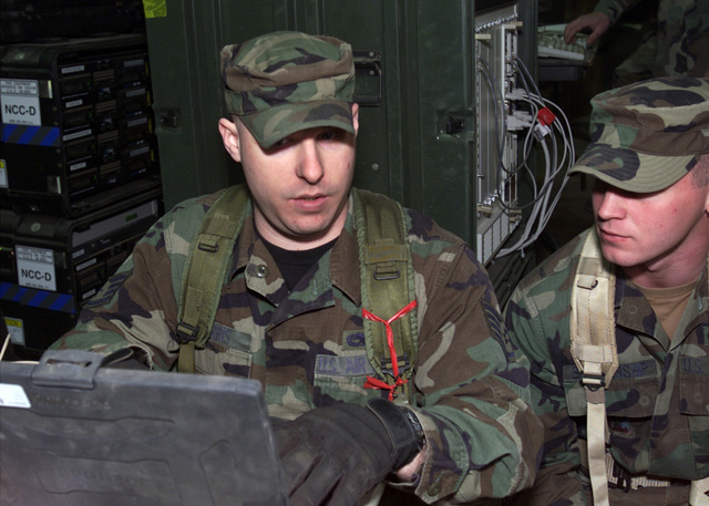 US Air Force (USAF) STAFF Sergeant (SSGT) John Harris (left) and USAF AIRMAN First Class (A1C) Dustin Blankenship, both assigned to the 5th Communications Squadron (CS), theatre deployable communications flight, program telephones into the switch at Minot Air Force Base (AFB), North Dakota (ND)