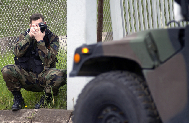US Air Force (USAF) STAFF Sergeant (SSGT) Ken Bergmann, a Photographer assigned to the 786th Communications Squadron (CS), documents activities at a security and customs check point at Ramstein Air Base (AB), Germany, during Exercise COMBINED ENDEAVOR 2002